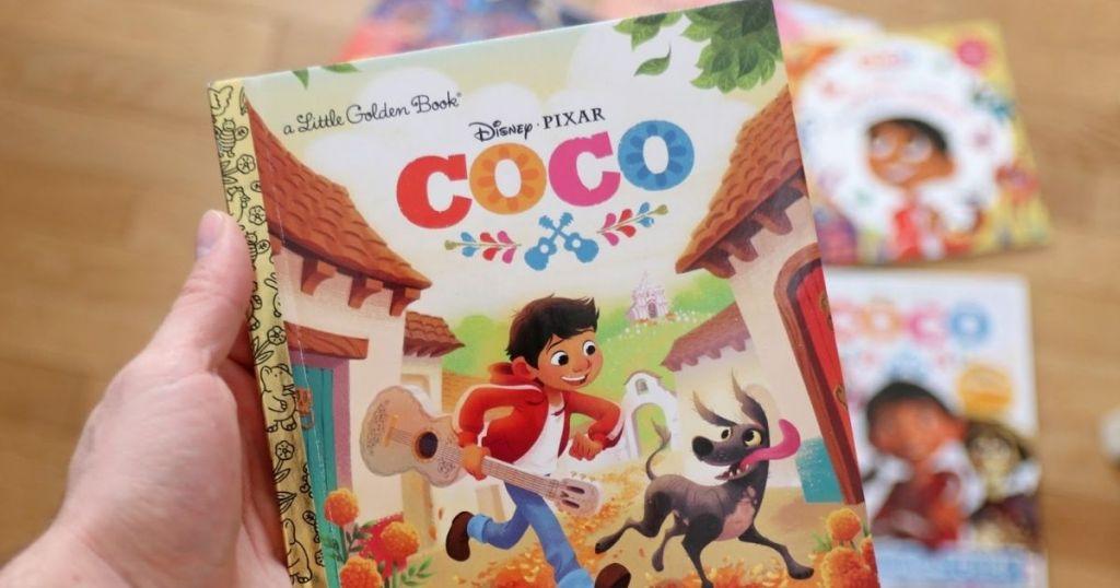 hand holding Disney Little Golden Books Coco