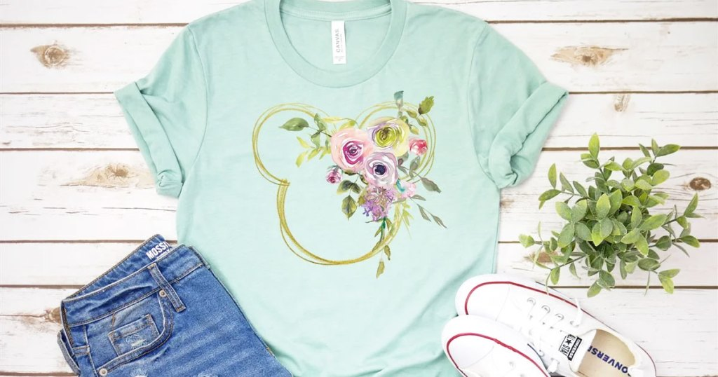 light blue tee with floral mickey mouse head graphic with jeans and converse shoes near it