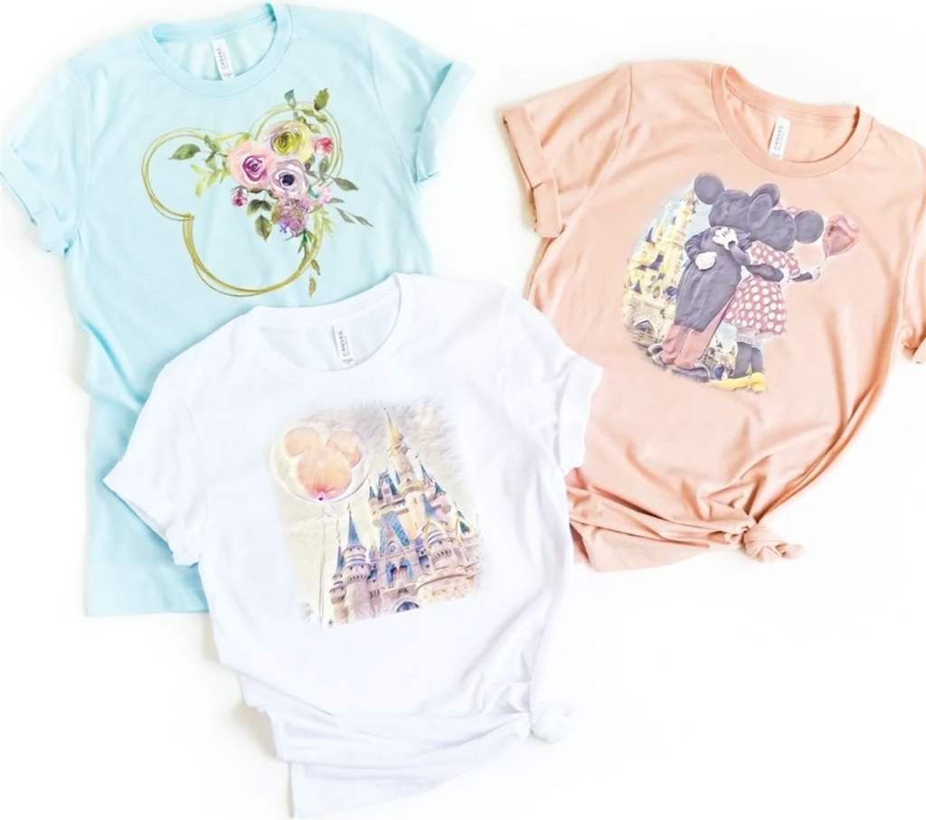 three women's tees in light blue, pink, and white with floral disney designs on them