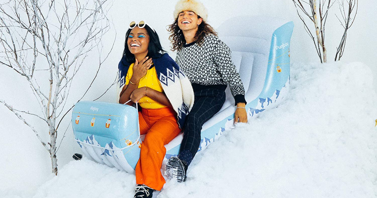 two people sitting on an inflatable sleigh going down a snowy hill
