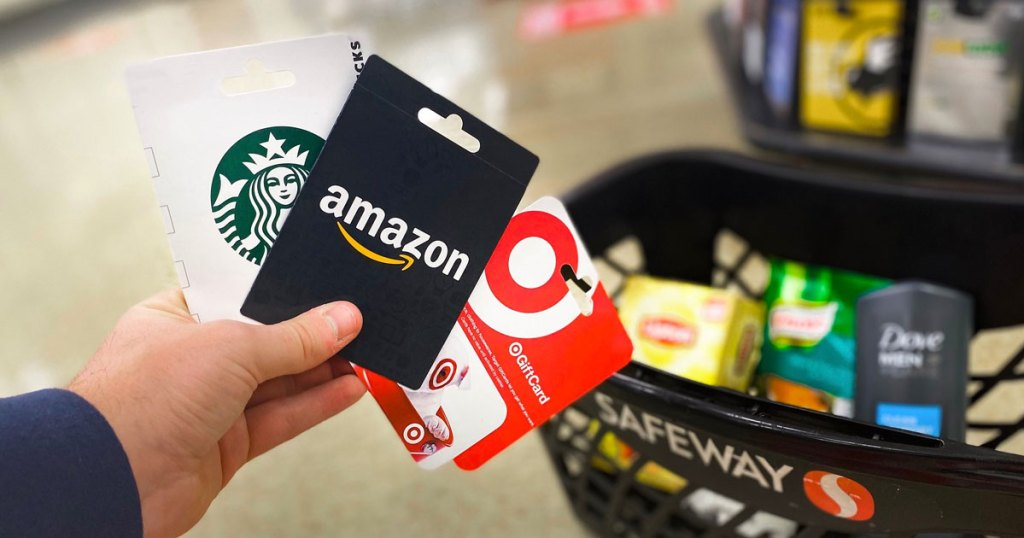 person holding starbucks, amazon, and target gift cards up in front of a safeway shopping basket