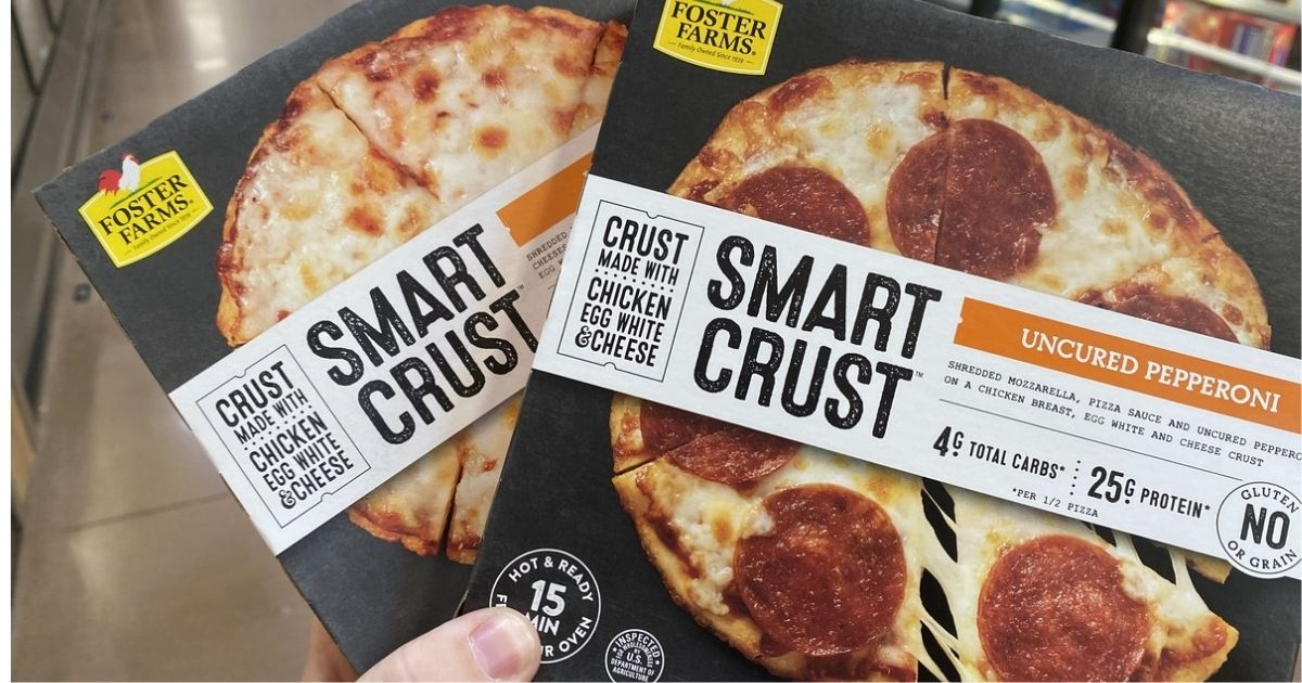 hand holding 2 Foster Farms Smart Crust Pizzas in store