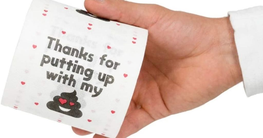 A hand holding a roll of toilet paper with a funny message on it