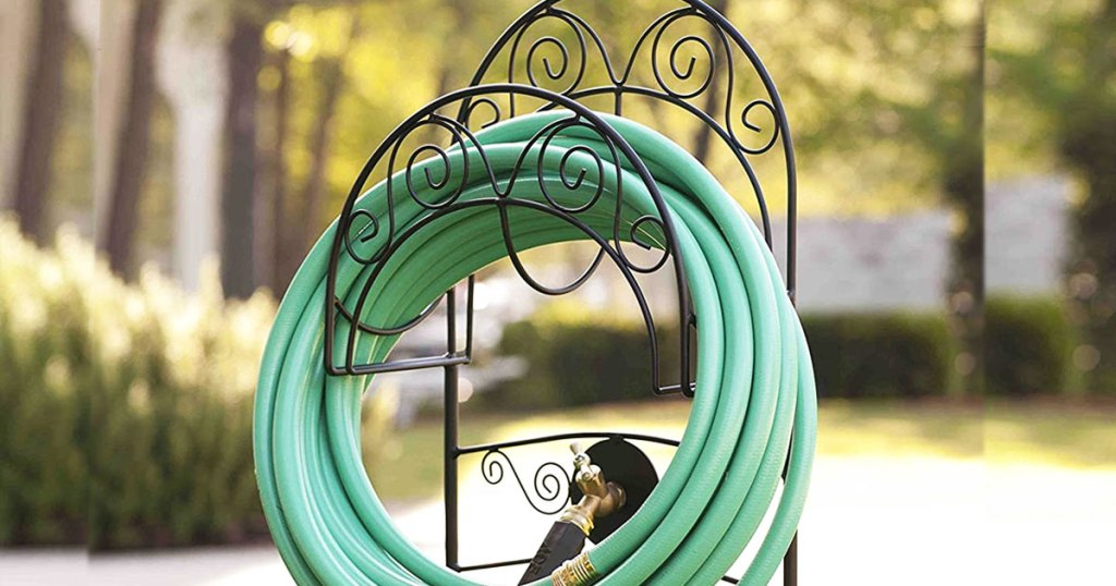 black metal garden hose stand with green hose coiled up neatly on it