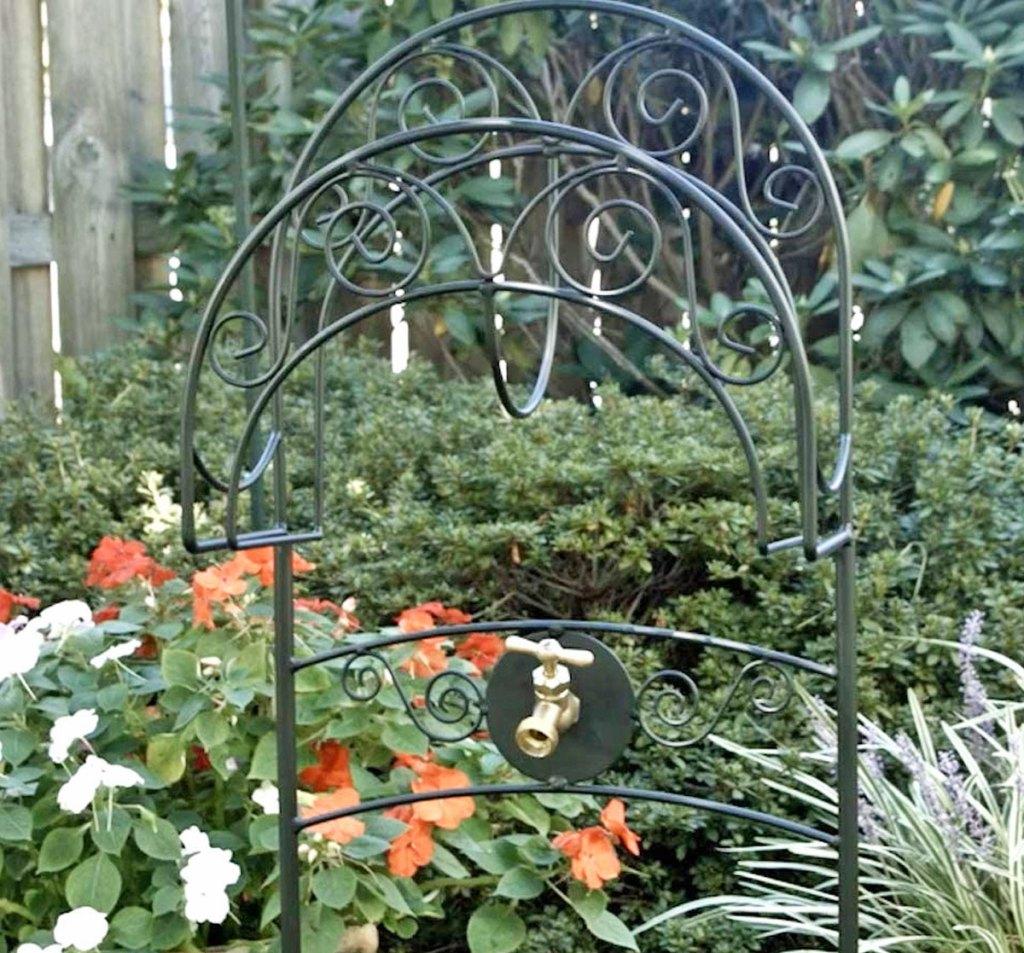 black metal garden hose stand placed in a garden