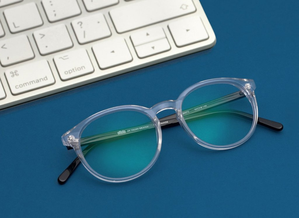 pair of glasses next to a white keyboard