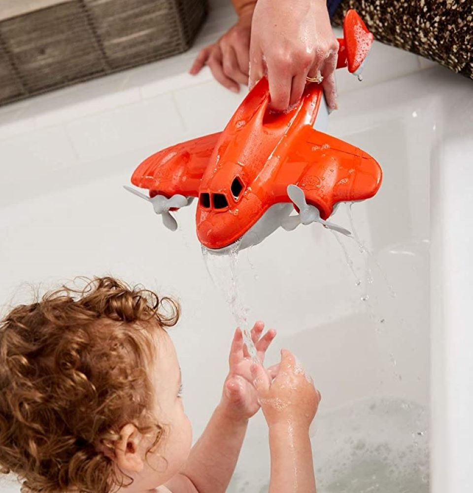 hand pouring water from a toy plane