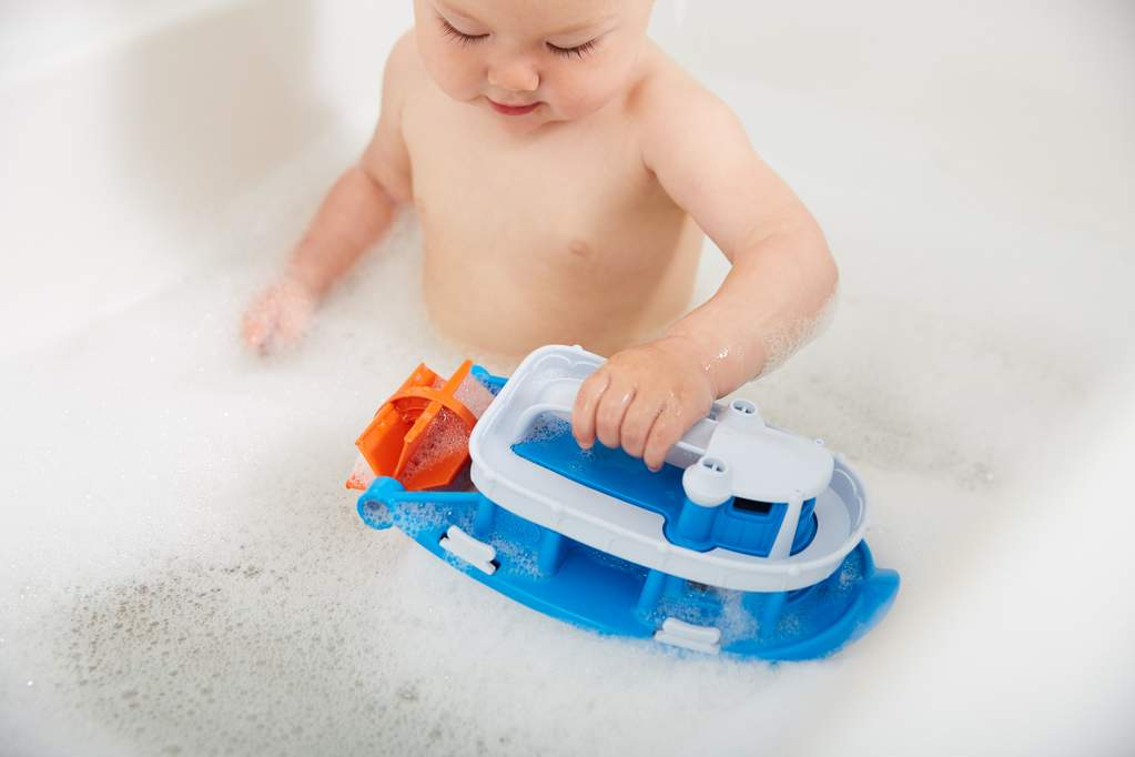 toddler playing with a boat in a tub