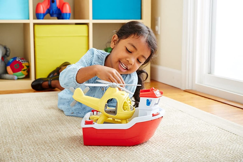 girl playing with a toy boat