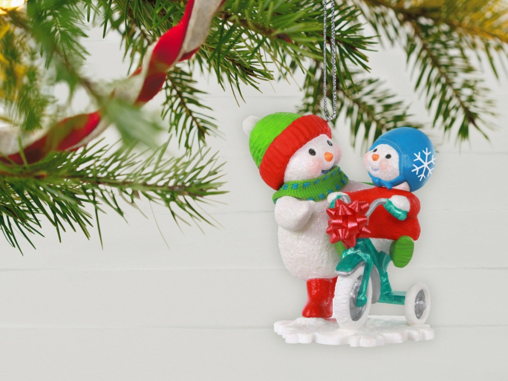 two snowmen standing next to each other one riding a trike