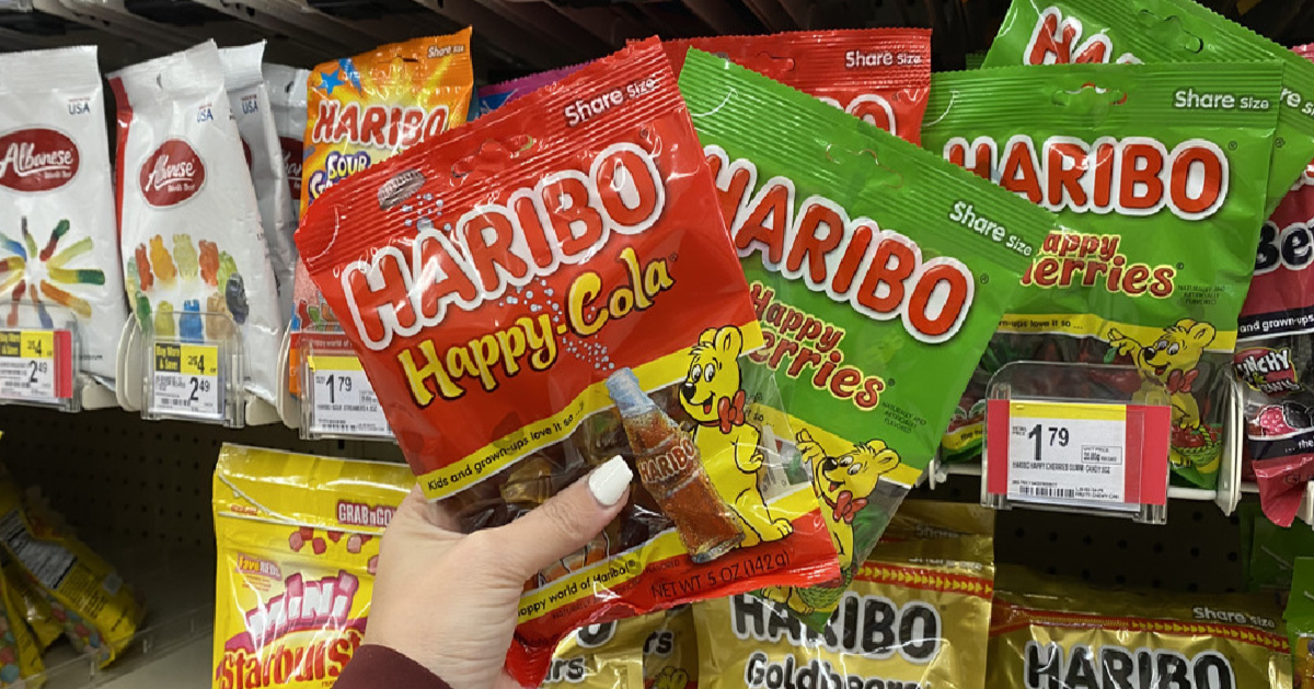 hand holding two bags of haribo gummy candy in front of a store display