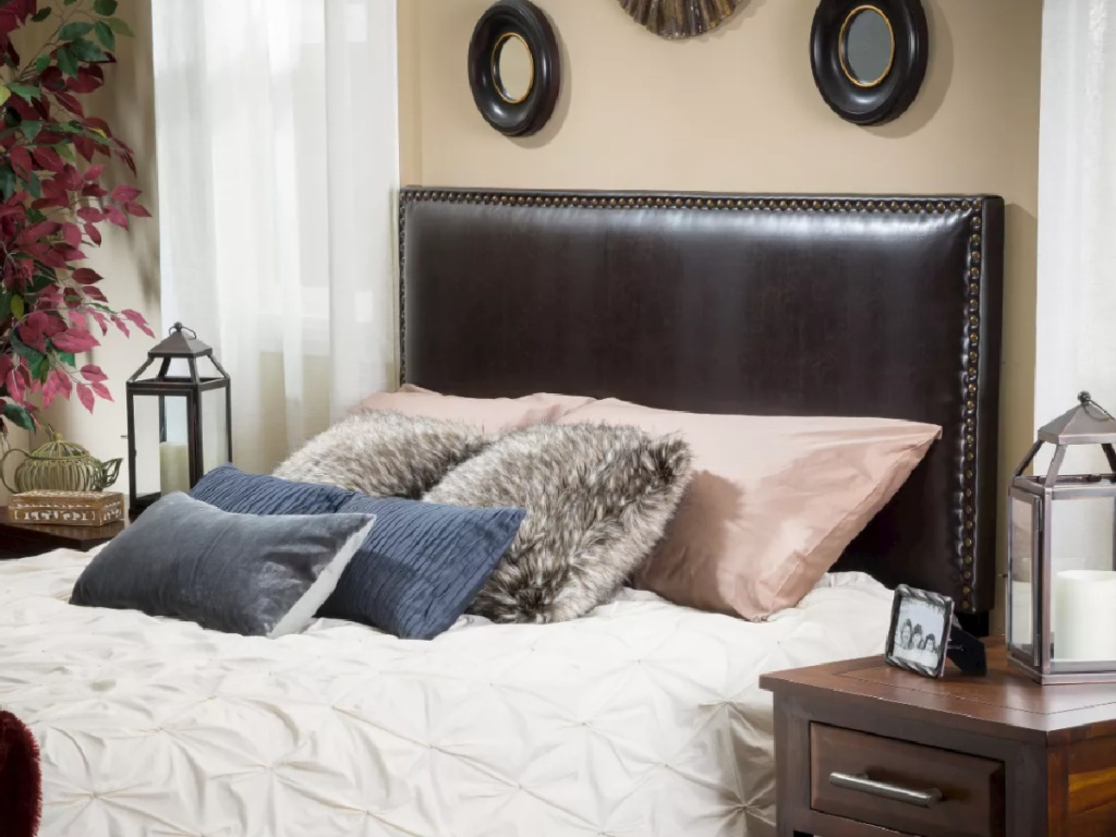 brown leather headboard attached to a bed in a bedroom
