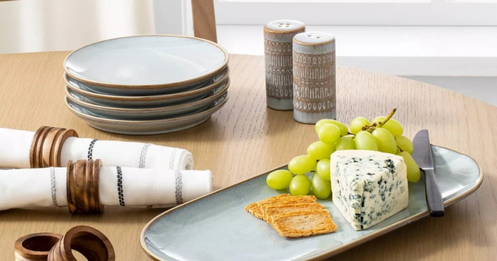 table with hearth and hand blue stone plates and seving plate with grapes and cheese
