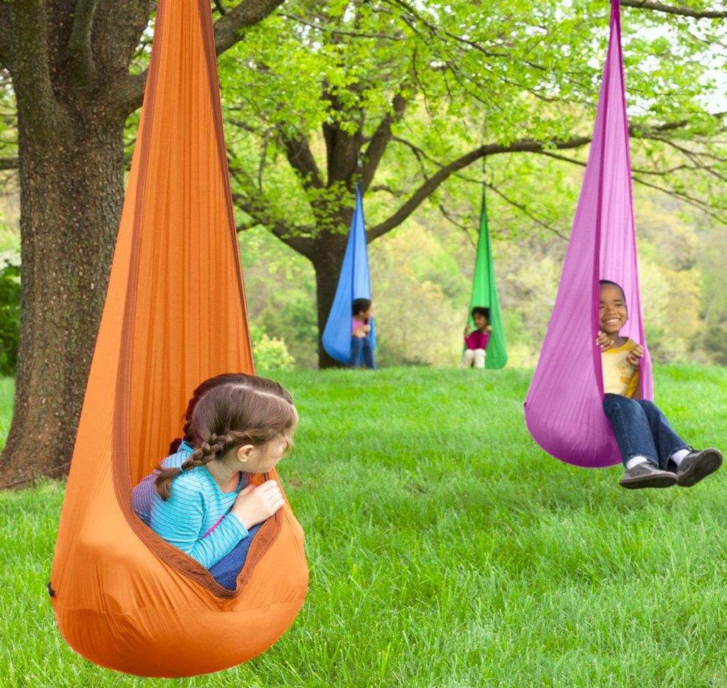 kids in nylon pod swings hanging from trees
