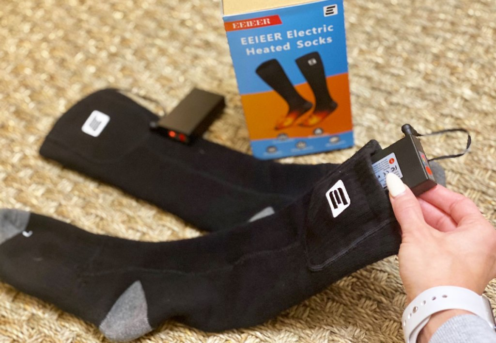 person holding the battery pack on a pair of black heated socks