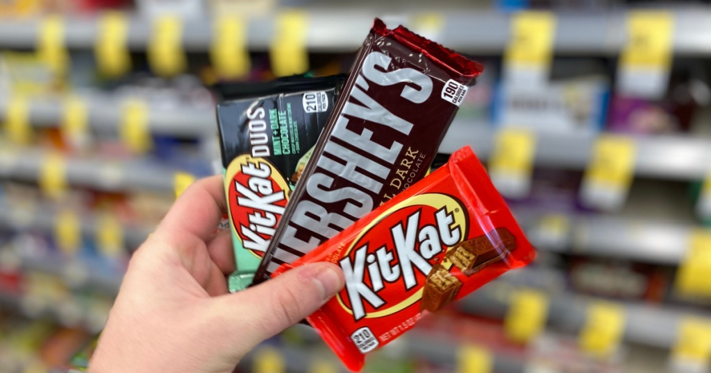 hand holding 3 hershey's candy bars at walgreens