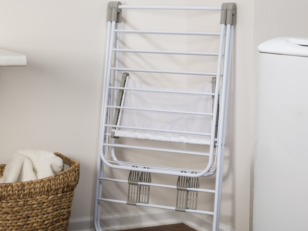 honey can do drying rack folded and leaning against a wall
