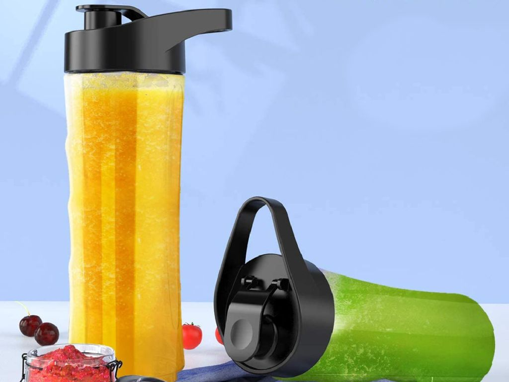 two blender bottles with fruit around them
