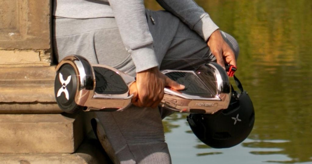 person in gray sweats holding Hover-1 Matrix Rose Gold Hover Board