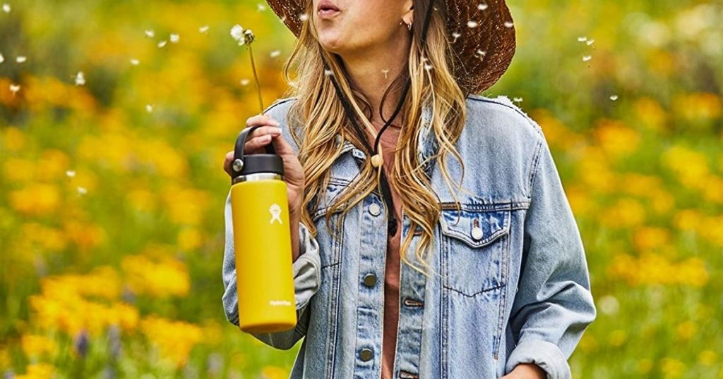girl in jean jacket holding yellow Hydro Flask 20oz wide mouth bottle blowing dandelions