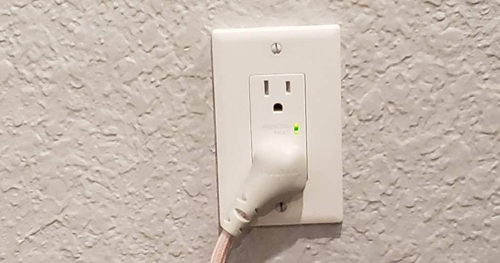 close up of Insignia 2-Outlet In-Wall Surge Protector in wall with cord plugged into one outlet