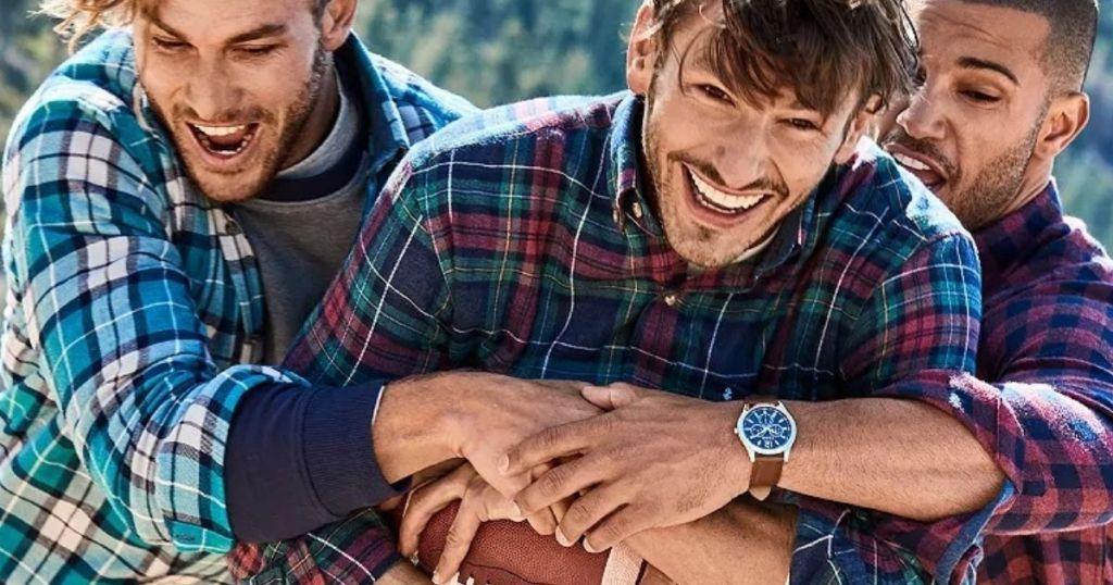 Men playing football wearing plaid shirts