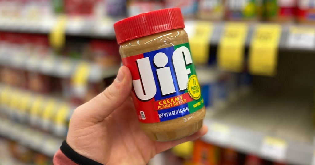 mans hand holding jar of peanut butter in store