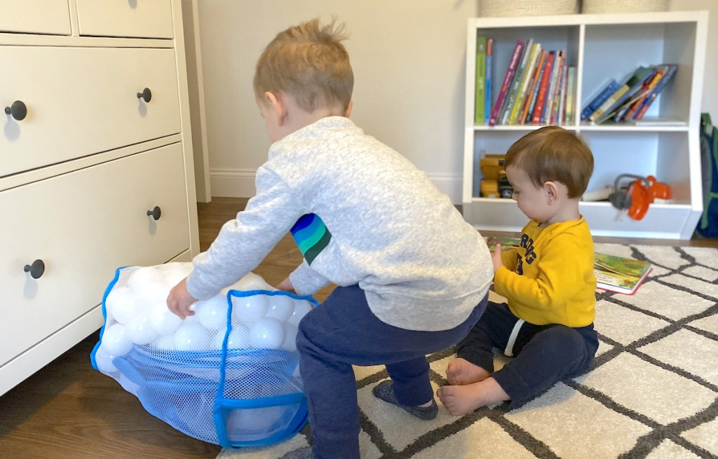 two little boys playing on rug with white plastic toy balls