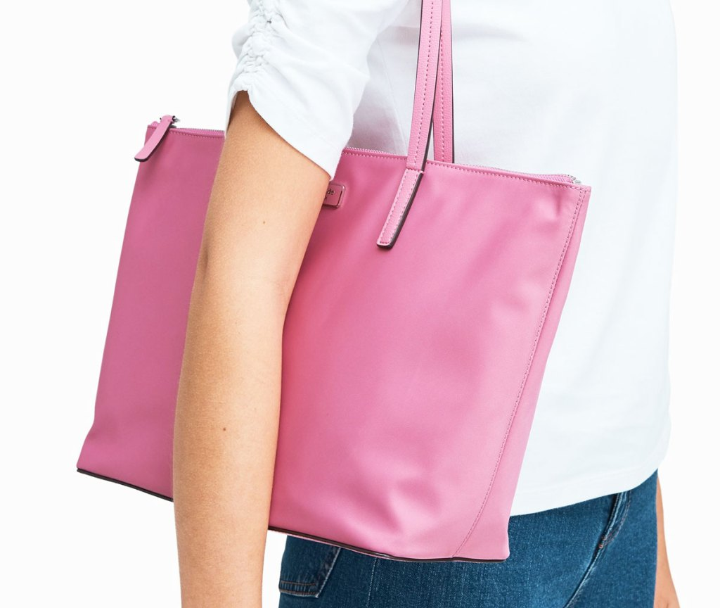 woman in a white shirt with a pink kate spade tote bag on her shoulder