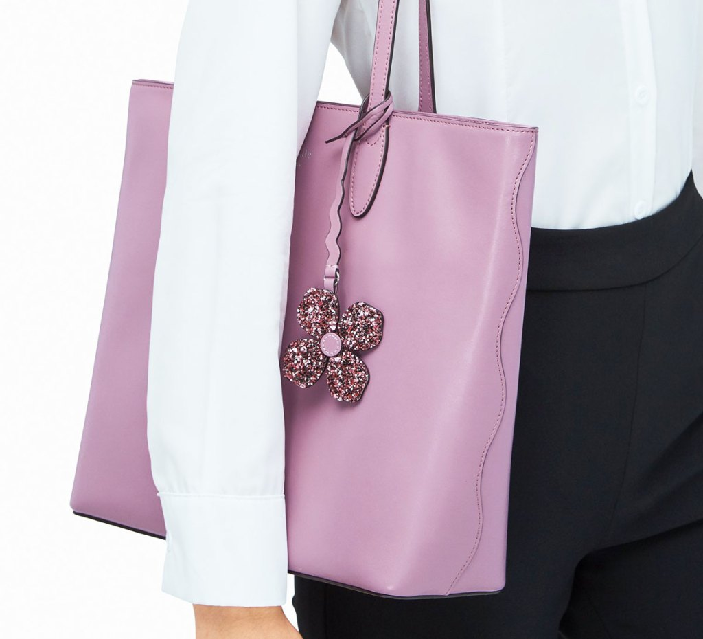 woman in white long sleeve shirt with purple tote bag on her shoulder