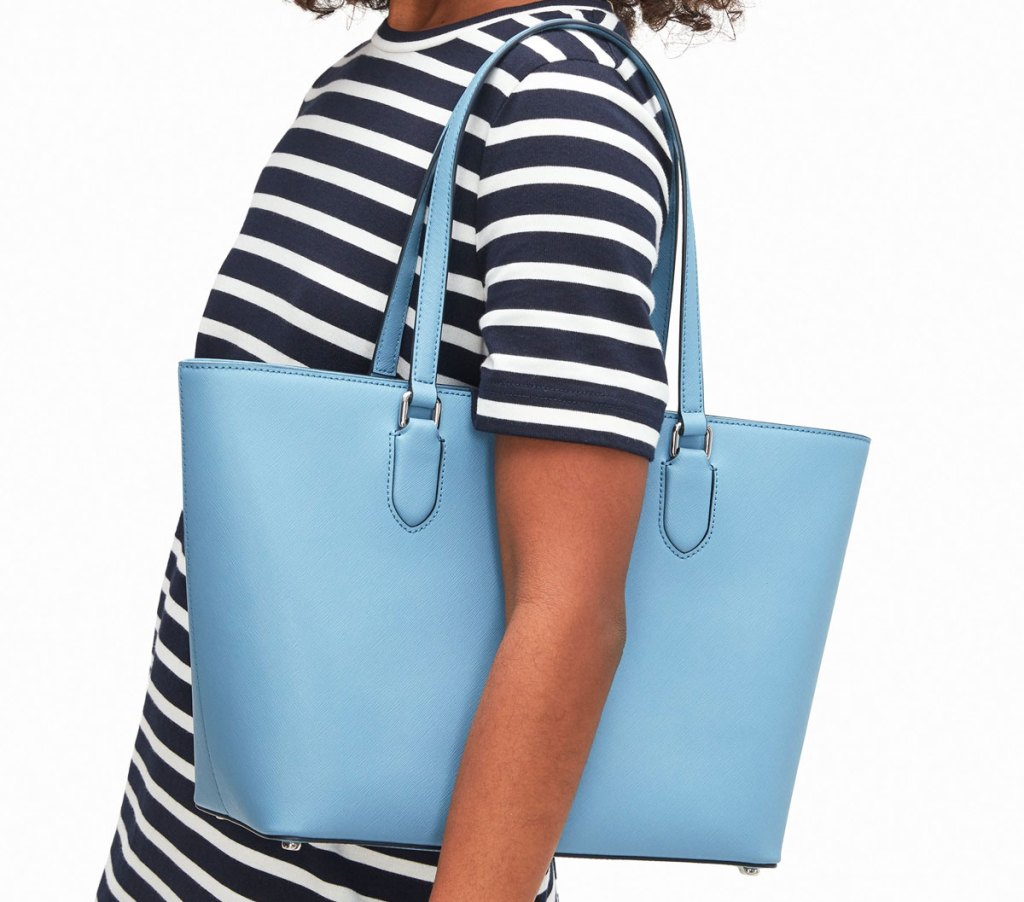 woman in white and black striped dress with blue tote bag on her shoulder