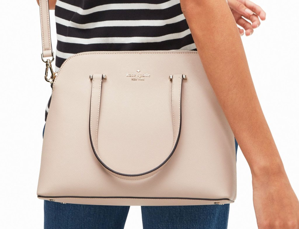 woman with a beige kate spade satchel at her hip