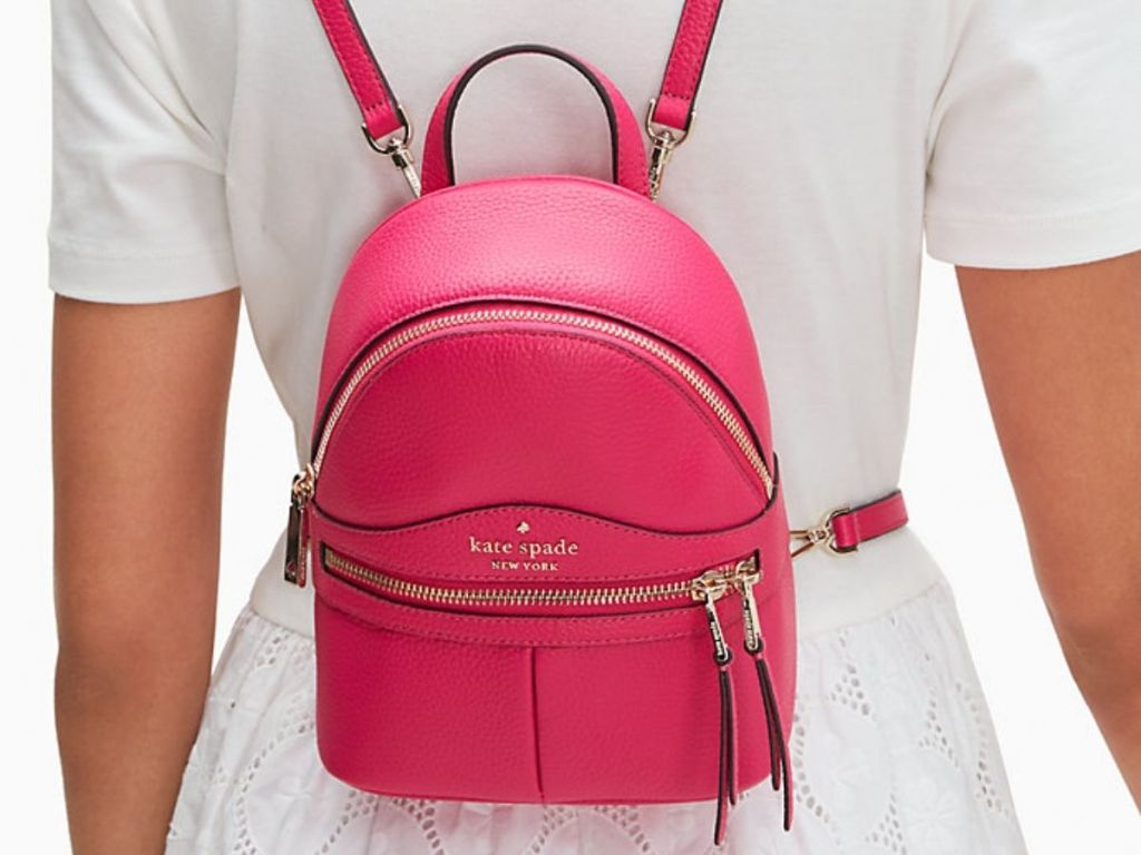 lady in white wearing Kate Spade Mini Backpack