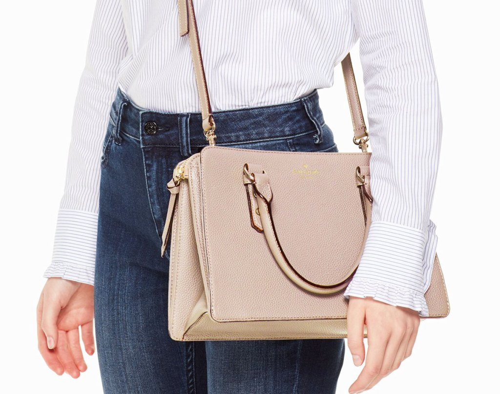 woman with a beige kate spade crossbody at her hip