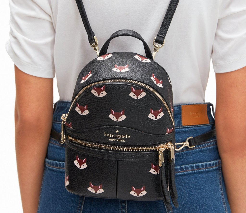 woman wearing a mini kate spade backpack with foxes printed on it