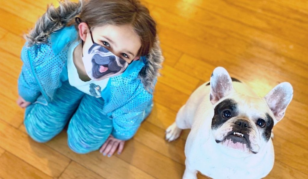 A little girl wearing a dog face mask sitting next to a dog