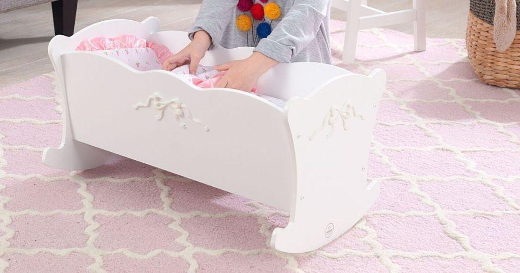 white wood doll crib in kids room