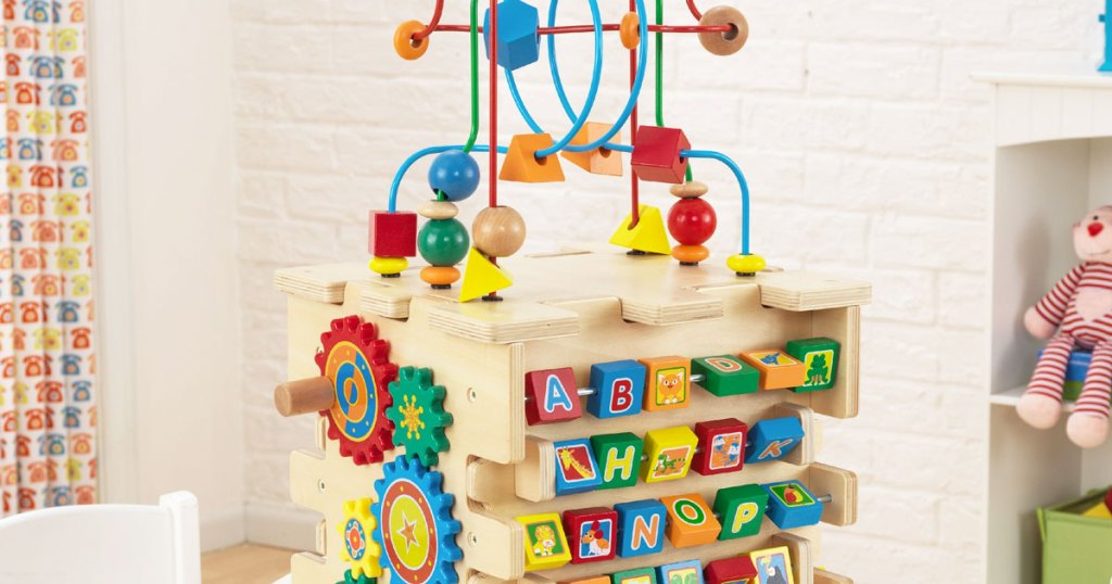 wooden activity center with spinning gears, alphabet letters, and sliding maze on top