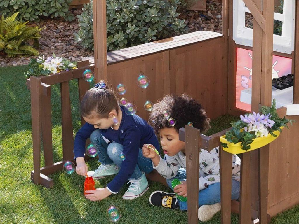 kids inside KidKraft Ryan's World Playhouse blowing bubbles