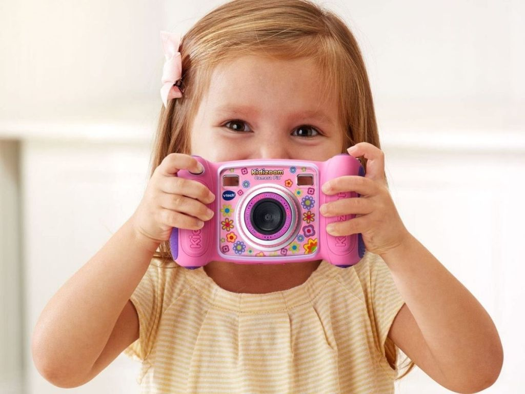 Little girl playing with toy camera