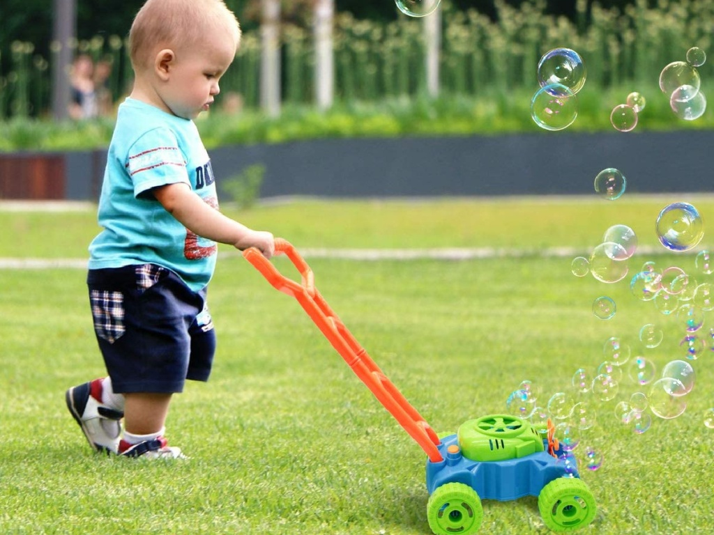 baby boy pushing a bubble mower outside in the grass