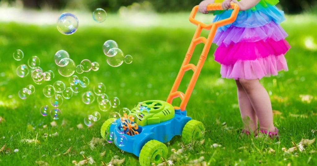 little girl pushng a bubble mower outside on the grass