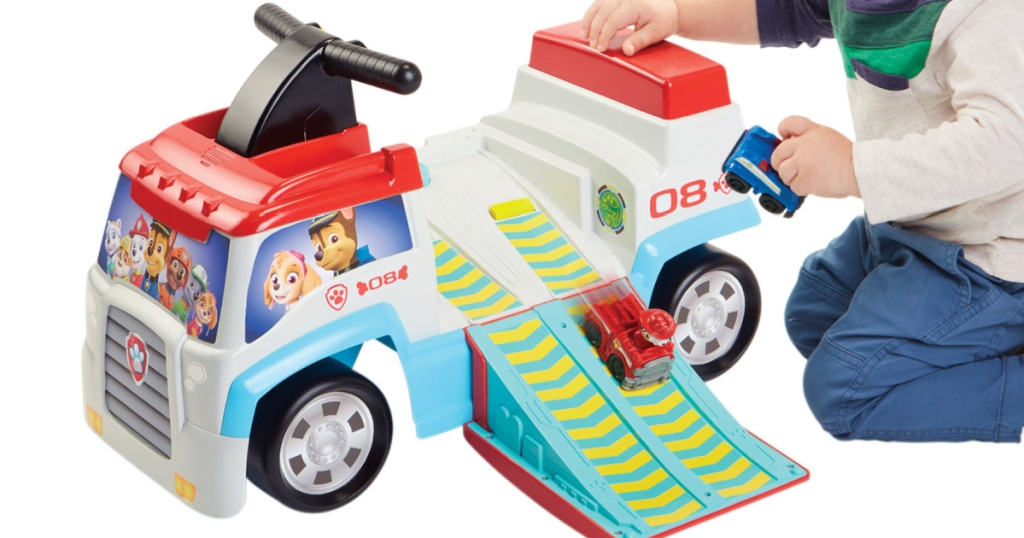 little boy kneeling next to a paw patrol ride on toy