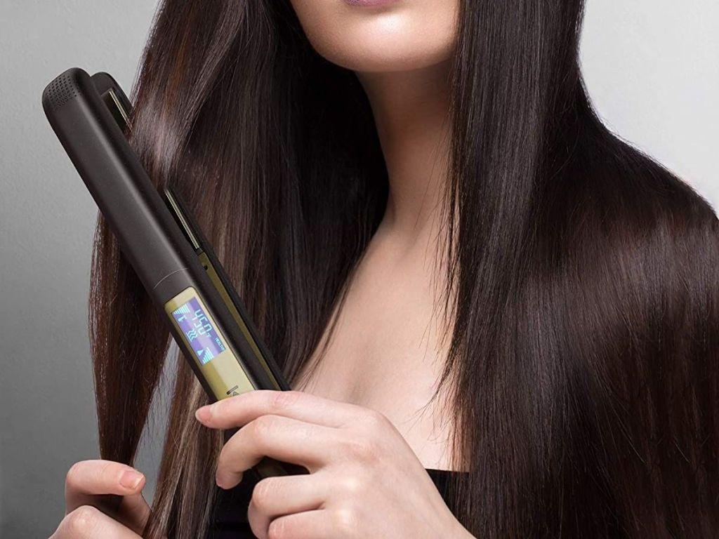 woman using black straightener on hair