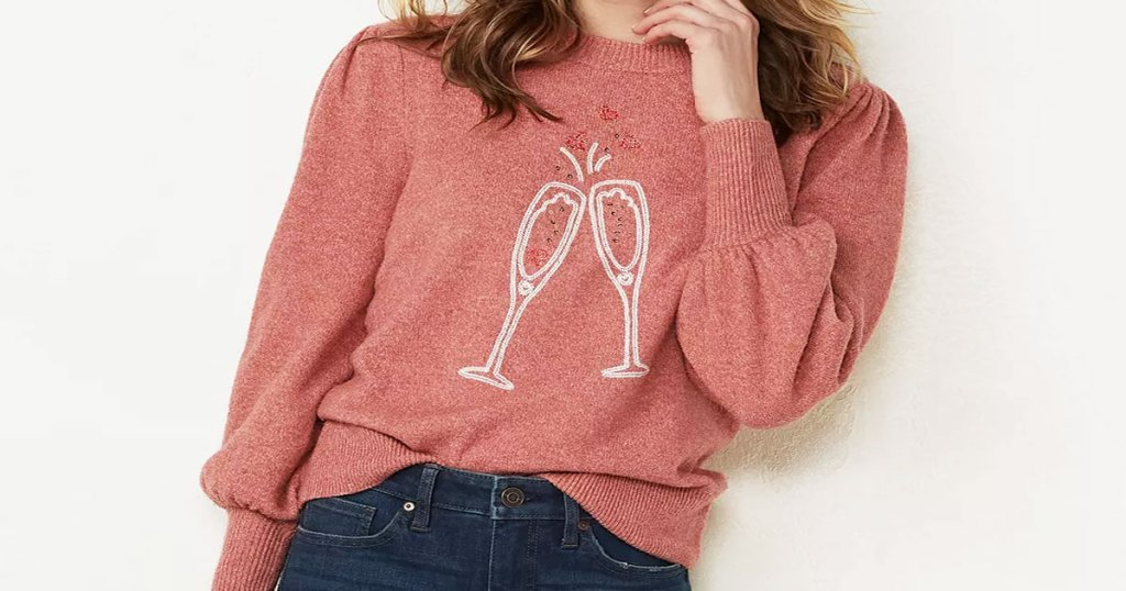 woman in a pink sweater with graphic of two champagne glasses clinking