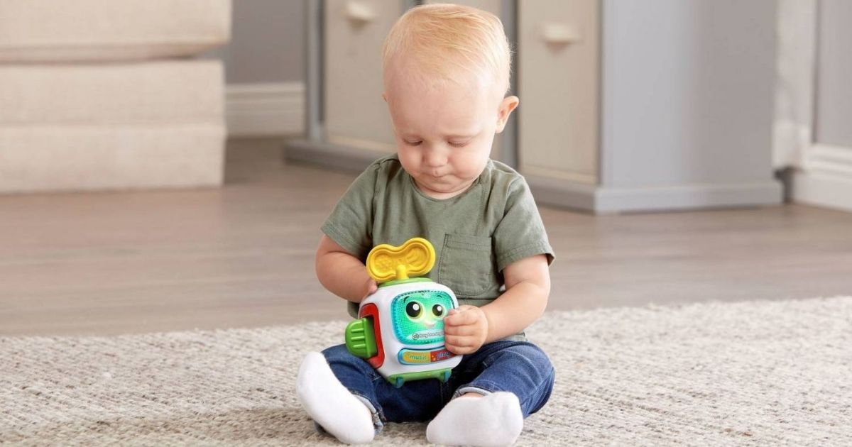 little boy playing with a Leapfrog Busy Learning Bot