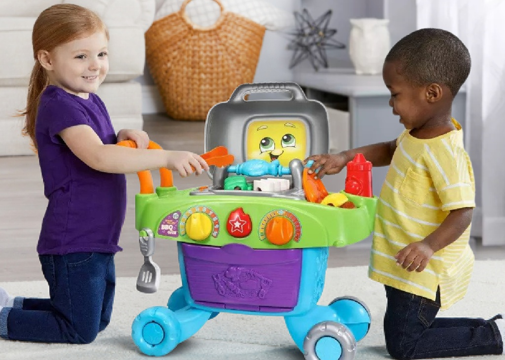 two kids playing with LeapFrog Smart Sizzlin' BBQ Grill