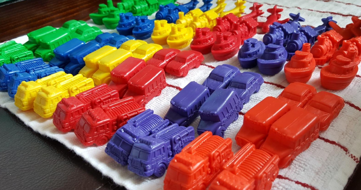 plastic toys grouped by color and type in rows on a kitchen towel