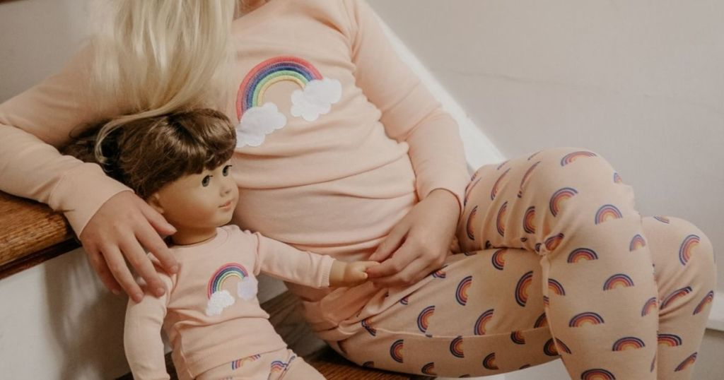 Little girl and doll wearing Leveret Marching Doll Set while sitting on stairs