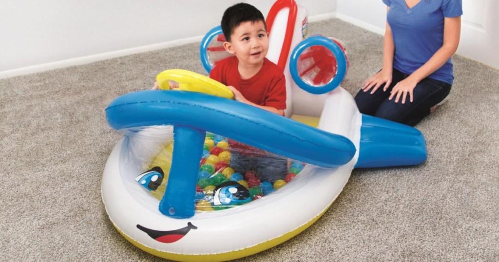 toddler boy in airplane ball pit